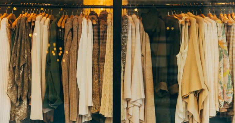 Tanti vestiti appesi in una vetrina di un negozio di abbigliamento